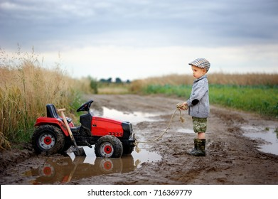 A little boy is playing with a tractor on a field muddy road