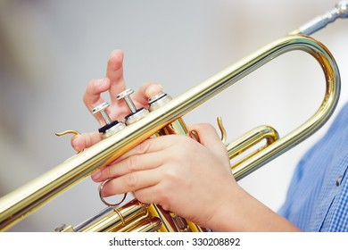 Little boy is playing the trumpet at home