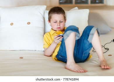 Little boy playing video games on portable console or mobile phone