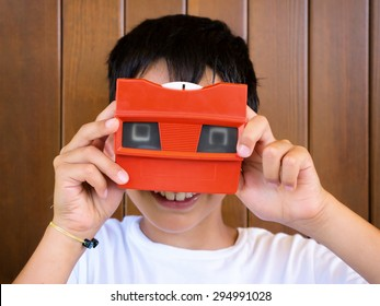 little boy playing with vintage 3d viewer