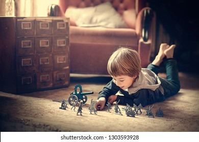 Little boy is playing with vintage toy soldiers. Image with selective focus, noise effect and toning.