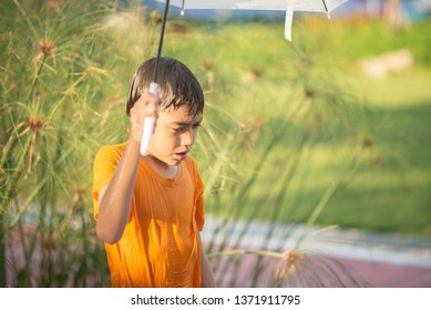 Little boy playing water drops fountain under the cloth and umbrella