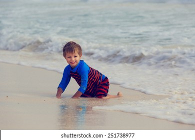 little boy playing with waves on summer sand beach