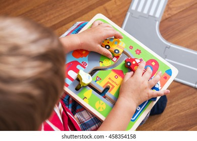 little boy plays board game with cars