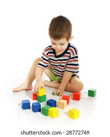 The little boy plays with color wooden cubes