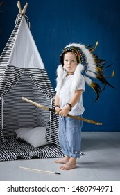 A little boy plays Indians with a bow and arrow in a big feather Mohawk next to a wigwam.