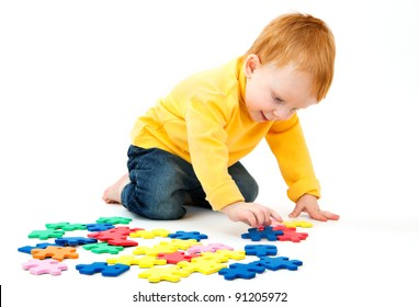 Little boy plays with a multi colored puzzle a white background