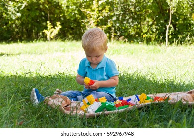 little boy plays with a constructor in nature. early childhood development