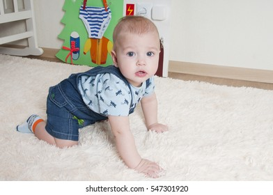 The little boy plays on a fur rug