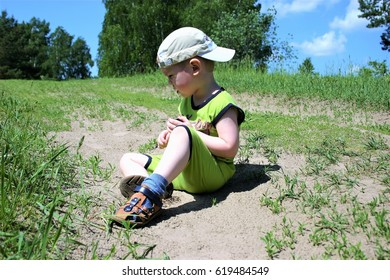A little boy plays on the lawn on a Sunny summer day.