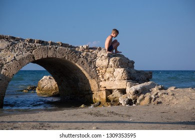 Little boy plays on a ruined old stone bridge next to a beach.