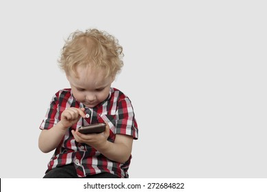 Little boy plays with smartphone on gray background with copy space - Modern gadgets and communication concept - Simplicity and usability