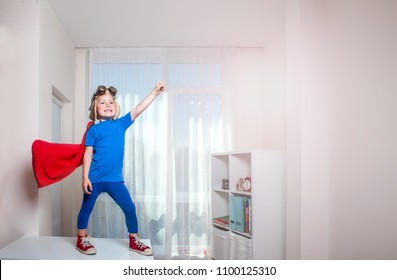 Little boy plays superhero at home. Child on white room background.