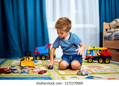 little boy plays with toy car at home