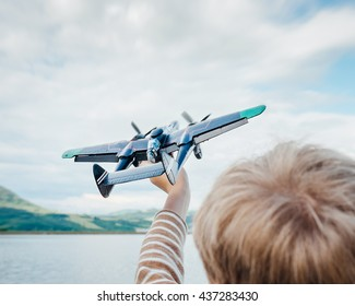 Little boy plays with toy military plane