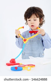 Little boy plays with toy phonendoscope and medical instruments on white background.
