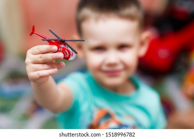 little boy plays with a toy red helicopter. In focus a hand with a toy, a boy in defocus