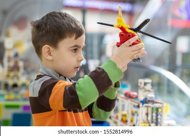 little boy plays with a toy red helicopter.the child is holding a helicopter constructor and looks at it with interest