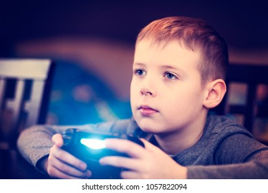 Little boy plays video game in the dark room