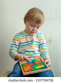 Little boy plays with wooden puzzle