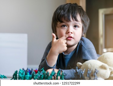 Little boy pointing finger on his nose and laying on the floor playing with soldiers and figurine toys in kid playroom, Active Kid playing wars and peace on his own at home,Imagination and Development