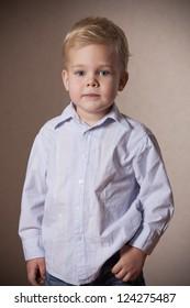 little boy portrait in shirt and jeans in studio