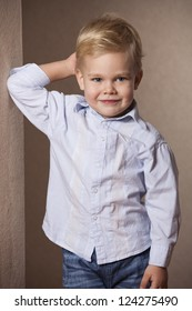 Little Boy portrait in shirt standing at the wall