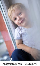 Little boy portrait at the window in rainy day