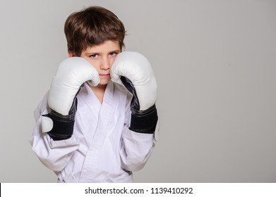 Little boy poses with boxing gloves on kimono. Karate.