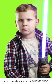 Little boy posing with a laser sword on a green background , blue bright light, a young boy with a serious face, an aspiring actor,