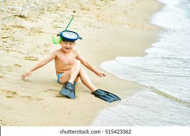 little boy posing on the beach wearing snorkeling equipment. On the background of the sea