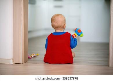 little boy posing in superhero costume