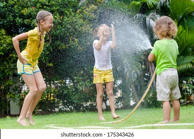 little boy is pouring a water from a hose at his sisters