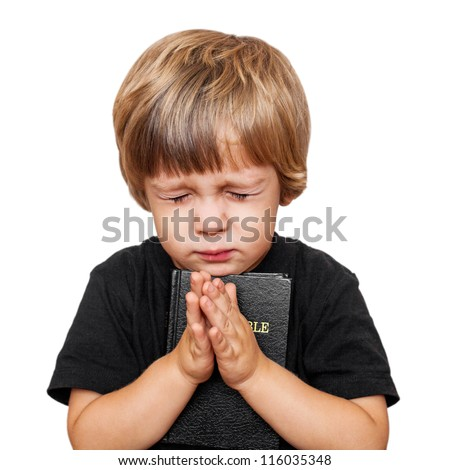 Little boy praying with the Bible in hand