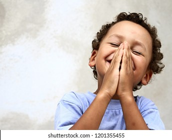 little boy praying to God with hands together and a smile on his face with head held high stock image stock photo