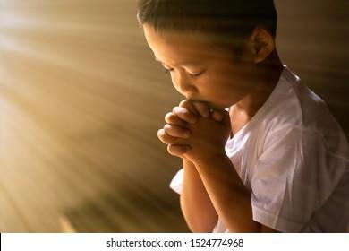 Kleiner Junge, der Gott betet mit Händen, die mit geschlossenen Augen zusammen gehalten werden