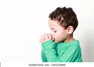 little boy praying with his hands clenched together