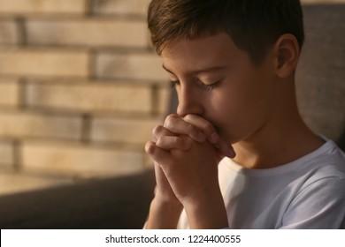 Little boy praying at home
