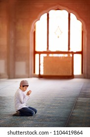 little boy praying in the mosque