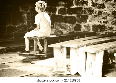 Little boy praying in old chapel. Retro aged photo. Sepia.
