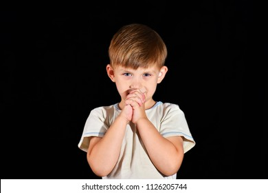 The little boy prays to God with his hands bent.