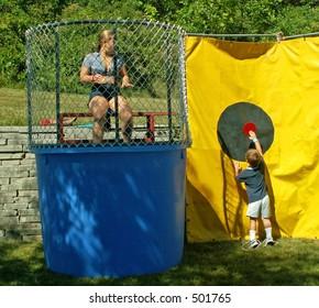 little boy pressing dunk tank button