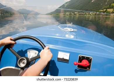 Little boy pretends to drive a boat on the lake