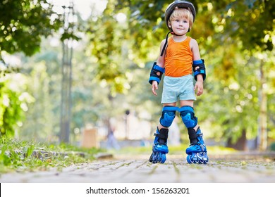 Little boy in protective equipment and rollers stands on walkway in park, low angle view