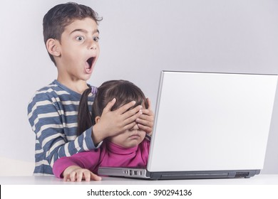 Little boy protects his sister from watching inappropriate content while using a computer. Internet safety for kids concept. Toned image with selective focus