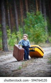 A little boy is pulling two huge suitcases along a deserted forest road - East or West, home is best.