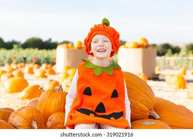 little boy in pumpkin costume enjoying pumpkin patch at autumn time, american tradition