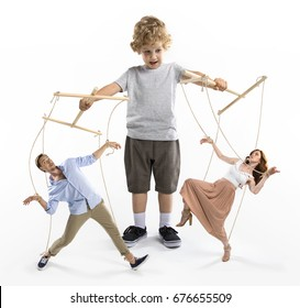 little boy puppeteer controlling parents with strings isolated on white