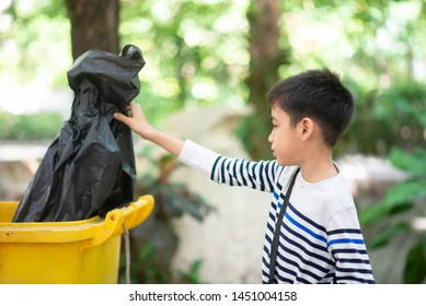 Little boy put the black garbage bag into the trash
