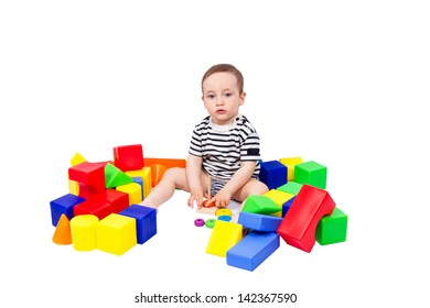 Little boy puts colored cubes and pyramid isolated on white background